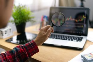 Investor looks at a stock chart on a laptop screen using a magnifying glass.