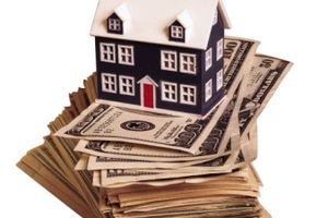 Model of house on stack of $100 bills