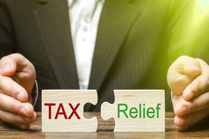 A Businessman Puts Two Puzzles With the Words Tax and Relief