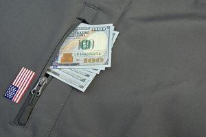 Money Pile Stuck Out Of Military Khaki Coat Pocket