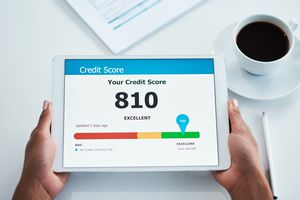 Two hands hold a tablet revealing a credit score of 810 Excellent.