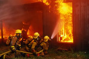 Firefighters with water hose controlling house fire