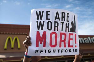 """Hands holding up sign in front of McDonald's: """"We Are Worth More! #FightFor15"""""""