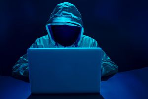 computer hacket in front of a laptop with their face concealed wearing a hood