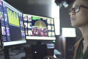 Investor reviews stock market data on several monitors