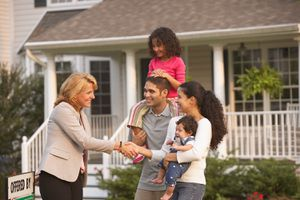 Hispanic family shaking hands with real estate agent in front of house