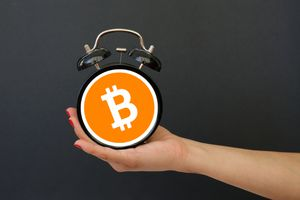 Person holds a clock with a Bitcoin symbol