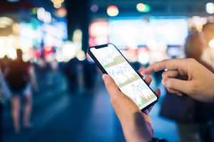 Close up of human hands checking financial stock charts on smartphone in busy city street, against neon commercial sign at night