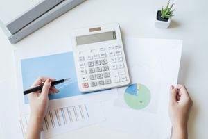 Businesswoman using a white calculator to calculate the value of business financial.