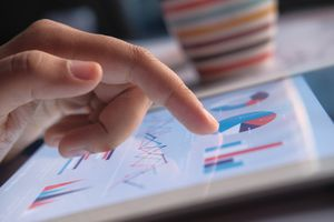 Women finger on ipad analyzing financial charts