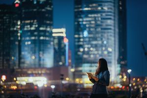 Young businesswoman using digital tablet looking back over at illuminated skyline