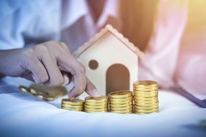 Woman stacking coins on table with miniature house on it