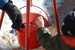 Nonprofit image of people putting coins in a red bucket