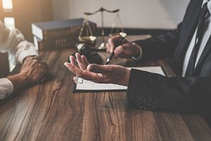 Midsection of Judge and Client Sitting at Table in Office