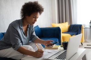 African American female using smartphone with a laptop and papers