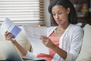 Woman looking shocked at a letter she is reading