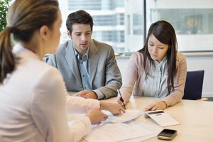 Young couple in office signing documents with business executive