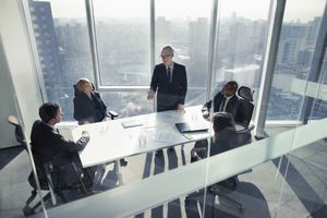 Businessman talking to colleagues in a boardroom meeting with the skyline visible through the windows