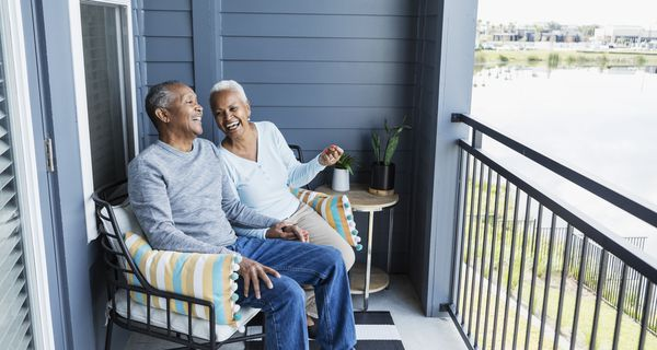 Senior couple relaxing on porch, holding hand, laughing