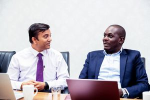 Two businessmen discussing in front of laptops.