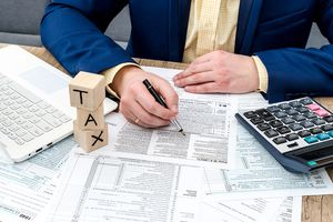 Businessman Filling W-4 Form With Pen, Calculator, and PC