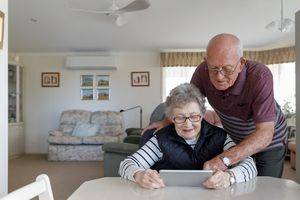 A couple watching a tablet in the living room.