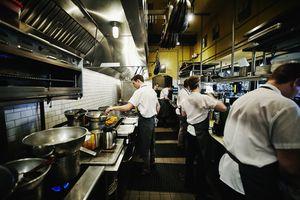 Chef and kitchen staff preparing dinner in kitchen