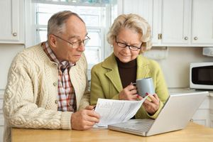 Older couple in kitchen, looking at computer with papers in hand