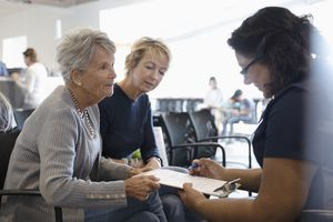 Female nurse explaining paperwork to senior patient and daughter in clinic waiting room