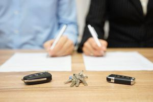 Man and woman signing documents on table with keys