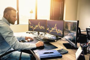 Young trader is working at stock market with three computer screen on his office desk.