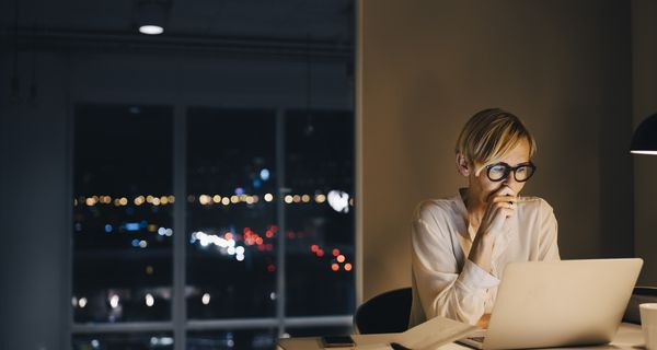 Stressed-looking mature businesswoman using laptop while sitting at illuminated desk in coworking space