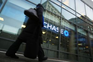 Person walking past glass bank building in front of Chase Bank logo