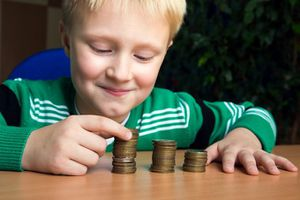 Little boy with 3 piles of coins