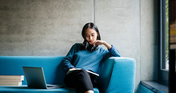 Young Woman Sitting On Couch In Library