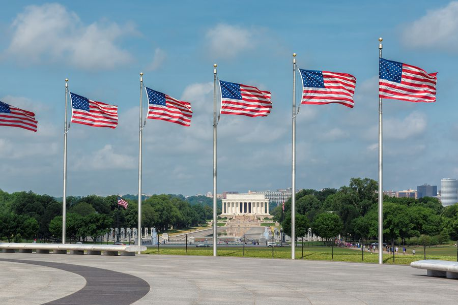 Lincoln Memorial with American flags from Washington Monument in Washington, D.C. at sunny day