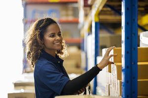 Warehouse worker arranges inventory on shelves