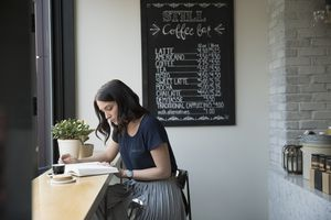 Woman reading book in café with chalkboard menu in background