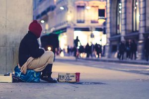 Homeless person sitting on city sidewalk, asking for money