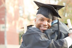 Black college graduate, with diploma, hugging friend