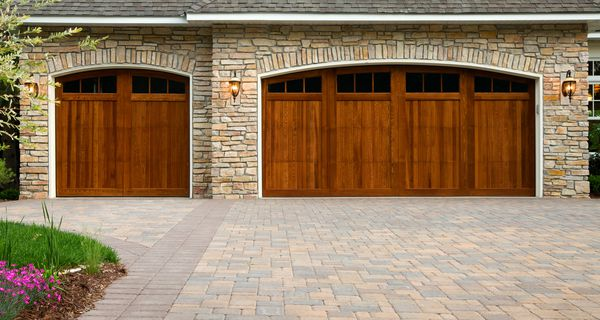 Pavers, wood custom garage doors, landscaping, and beautiful stone exterior walls on a custom home.