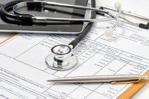 Medical bills, stethoscope, pen