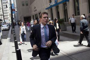 Man on street near Wall Street and New York Stock Exchange