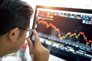 Man analyzes stock market graph on computer screen.