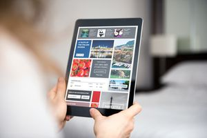 Person looks at advertisements and articles on a tablet.
