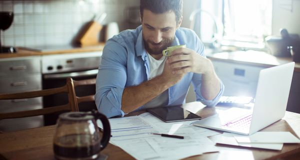 A man sits with his elbows resting on a kitchen table, which is bestrewn with papers, a calculator, and an open laptop; he clutches a cup of coffee and grins slightly at the good news that debt relief is near at hand.
