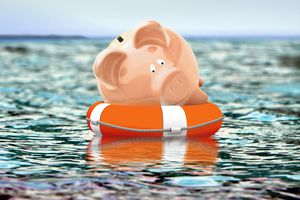 Emergency fund image of piggy bank on life preserver in the sea.