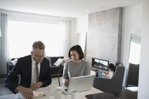 Financial advisor and woman with laptop meeting in dining room