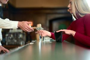 Woman at a counter, paying money to bartender