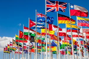 Flags from many different nations against a blue sky